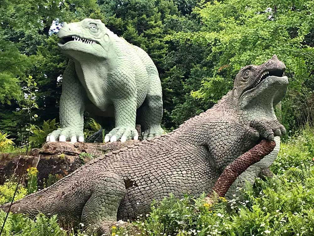 2 dinosaur sculptures in greenery