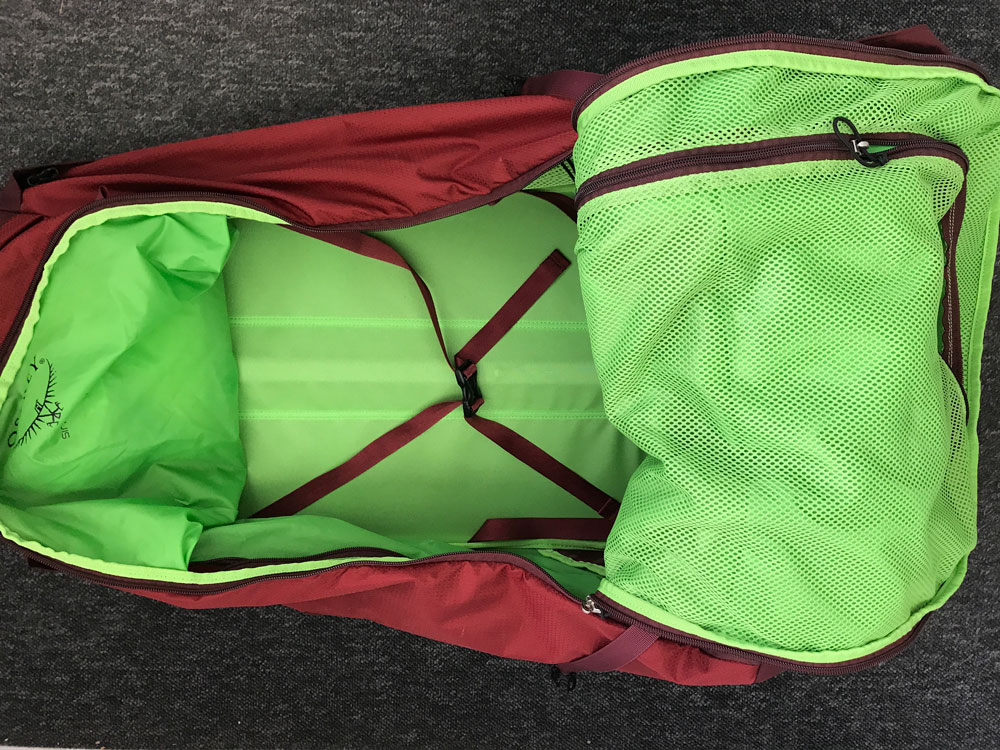 red and green interior of osprey ozone 75 backpack on wheels