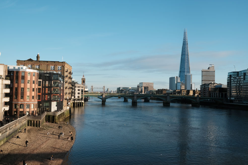 the shoreline of river thames looking towards the shard and london bridge